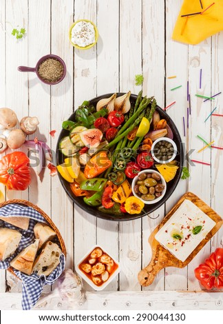 High Angle View of Colorful Grilled Vegetable Platter on White Picnic Table Surrounded by Fresh Bread and Cheese at Outdoor Party - stock photo