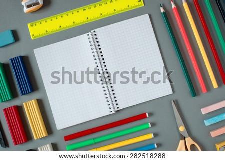 High Angle View of Colorful School Supplies Organized by Type Around Note Book Open to Blank Page Arranged on Grey Desk - stock photo