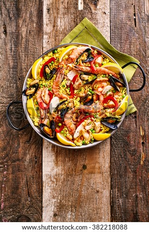 High Angle View of Colorful Seafood Spanish Paella Rice Dish with Shrimp and Mussels Shellfish Garnished with Fresh Lemon and Served in Pan with Green Napkin on Rustic Wooden Table with Copy Space - stock photo