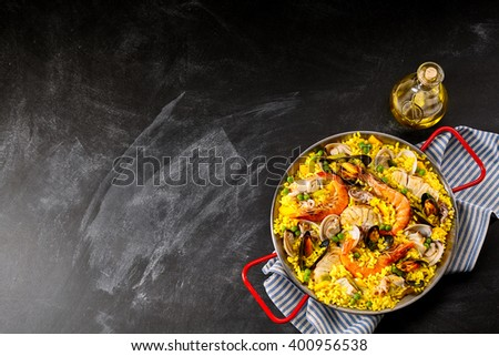 High Angle View of Colorful Spanish Seafood Paella Rice Dish with Fresh Shrimp Scampi Served in Pan with Handles with Oil and Napkin on Smudged Chalkboard Background with Copy Space - stock photo
