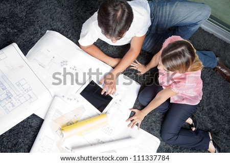 High angle view of couple sitting on rug with blueprints and digital tablet - stock photo