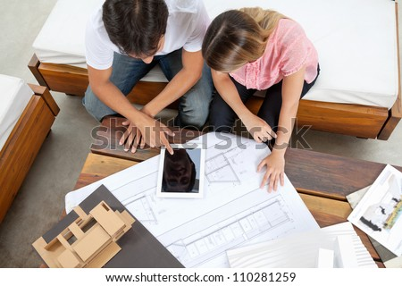 High angle view of couple using tablet PC with blueprint and model structure on table