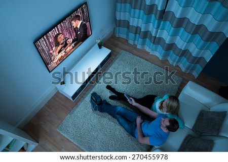 High Angle View Of Couple Watching Movie In Living Room - stock photo