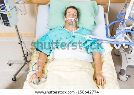 High angle view of critical patient with endotracheal tube resting on bed in hospital - stock photo