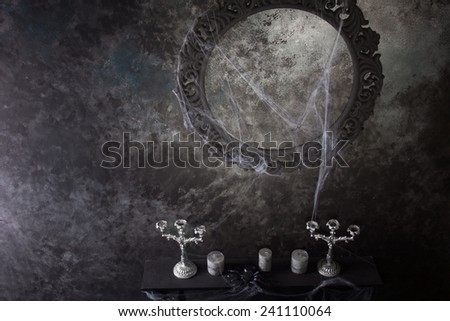High Angle View of Decorative Round Frame Above Candles and Candelabras on Eerie Cobweb Covered Mantle in Haunted House Setting - stock photo