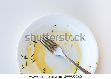 High angle view of dirty white plate with fork across it on white background (cropped) - stock photo
