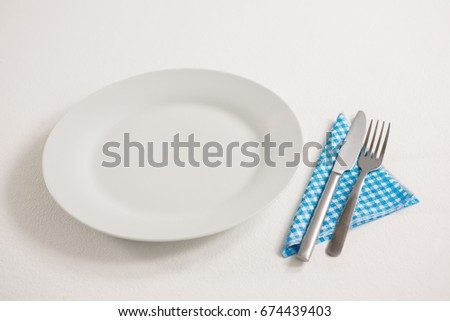 High angle view of empty plate with eating utensils and napkin on table