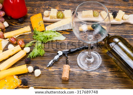 High Angle View of Empty Wine Glass and Bottle of White Wine on Rustic Wooden Table Amongst Gourmet Cheeses and Fruit - stock photo