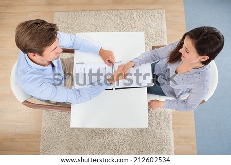 High angle view of female candidate shaking hand with businessman in office - stock photo