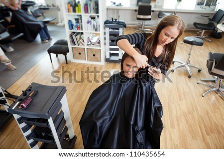 High angle view of female customer getting hair cut by beautician at parlor