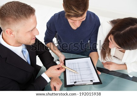 High angle view of financial advisor explaining investment plan to couple at office desk - stock photo