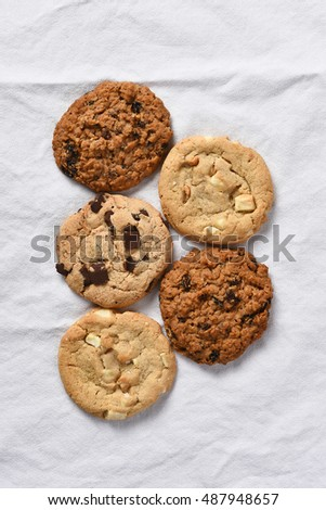 High angle view of five assorted cookies. Vertical format on a white kitchen towel.