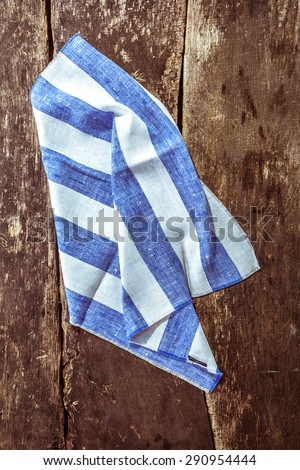 High Angle View of Folded and Crumpled Blue and White Striped Linen Napkin on Rustic Wooden Table Surface - stock photo