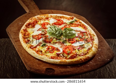 High Angle View of Fresh Baked Margherita Pizza Topped with Tomatoes, Cheese and Fresh Basil on Wooden Paddle - stock photo
