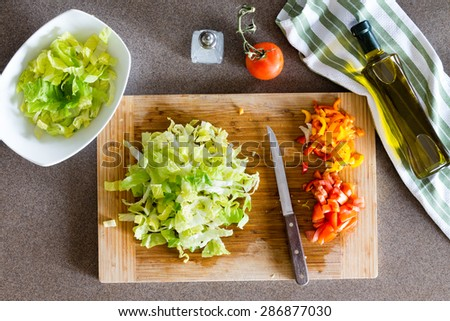 High Angle View of Fresh Healthy Chopped Vegetables on Top of Wooden Cutting Board with Knife for Healthy Salad - stock photo