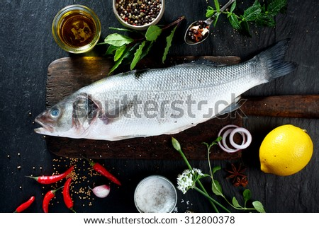 High Angle View of Fresh Raw Whole Fish on Rustic Wooden Cutting Board Surrounded by Fresh Herbs and Spices for Seasoning and Garnishing - stock photo