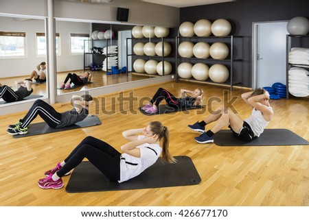 High Angle View Of Friends Doing Situps - stock photo