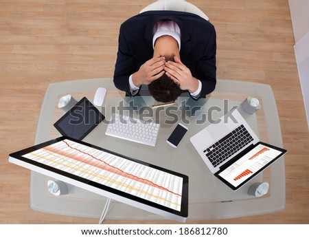 High angle view of frustrated businessman sitting at office desk - stock photo