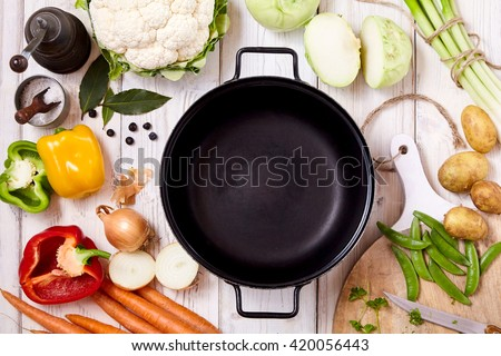 High Angle View of Frying Pan Wok Surrounded by Fresh Raw Vegetables and Spices Arranged Randomly on Painted Wooden Table Surface