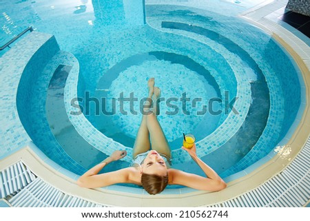 High angle view of girl sitting in swimming pool - stock photo