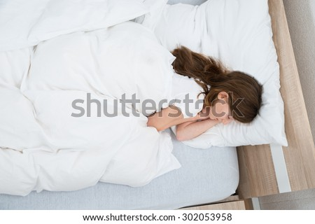 High Angle View Of Girl Sleeping On Bed In Bedroom - stock photo