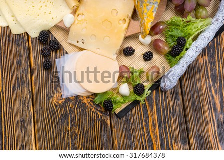 High Angle View of Gourmet Cheese Board Featuring Variety of Cheeses and Garnished with Fresh Fruit, Served on Rustic Wooden Table with Copy Space - stock photo