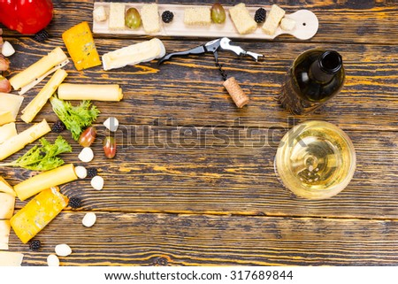 High Angle View of Gourmet Cheeses and Fresh Fruits with Glass of White Wine and Bottle on Rustic Wooden Table with Central Copy Space - stock photo