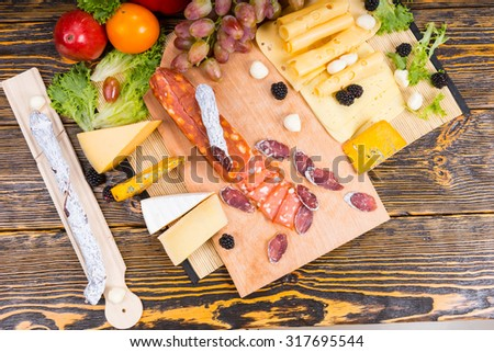 High Angle View of Gourmet Meat and Cheese Board Featuring Variety of Cheeses and Garnished with Fruit Served on Rustic Wooden Table - stock photo