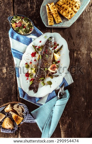 High Angle View of Grilled and Garnished Whole Fish on Wooden Table Surrounded by Other Dishes and Linen Napkins - stock photo