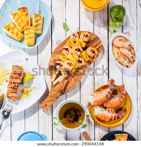 High Angle View of Grilled Fruit and Seafood Dishes Arranged on White Wooden Table Surface - stock photo