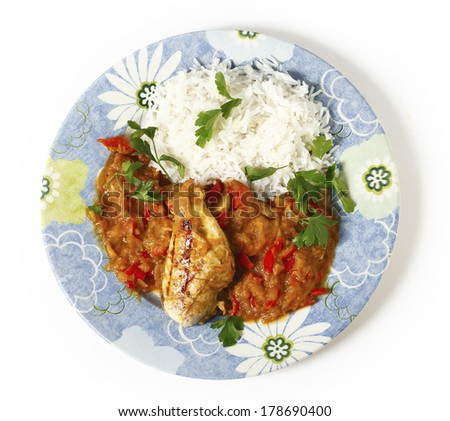 High angle view of grilled marinaded chicken served with a spice tomato and red capsicum salsa, in the Caribbean style, and white rice, all garnished with parsley. - stock photo