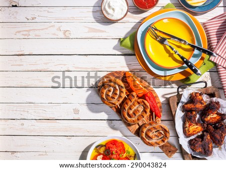 High Angle View of Grilled Sausages and Chicken Wings on Picnic Table with Colorful Plates and Cutlery, Copy Space on Table with Barbequed Meal - stock photo