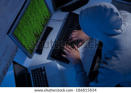High angle view of hacker in hooded jacket using computer at table - stock photo