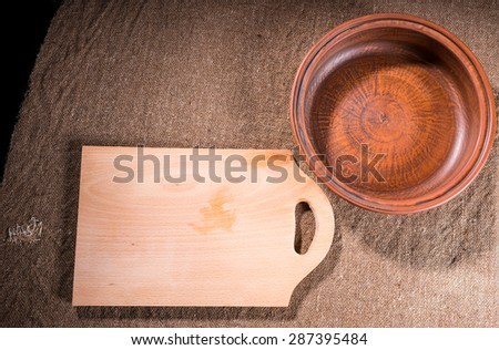 High Angle View of Handcrafted Wooden Cutting Board and Carved Wood Bowl on Burlap Covered Table Surface as seen from Directly Above - stock photo