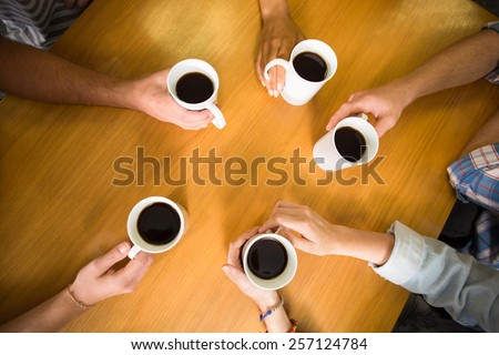 High angle view of hands holding coffee mugs on table - stock photo
