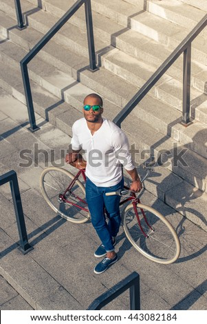 High angle view of handsome young Afro American man in casual wear and sun glasses leaning on his bike while standing on stairs outdoors - stock photo