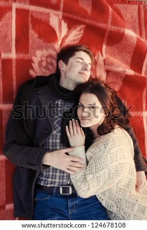 High angle view of happy couple enjoying together while lying on plaid - stock photo