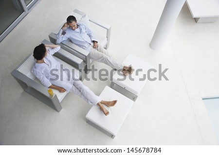 High angle view of happy couple sitting on armchairs with feet on foot stools in modern house - stock photo