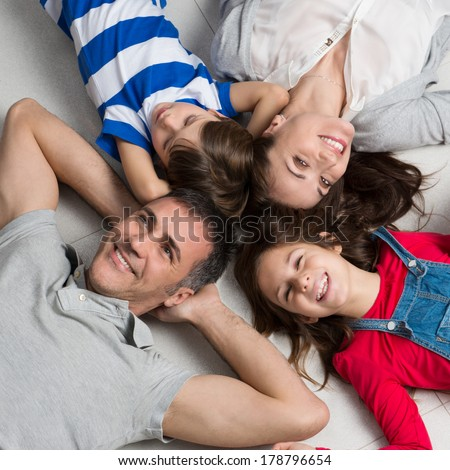 High Angle View Of Happy Family With Two Children Lying On Floor - stock photo