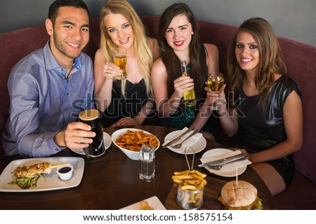 High angle view of happy friends having dinner together looking at camera - stock photo