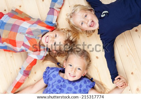 High angle view of happy little siblings lying on hardwood floor - stock photo