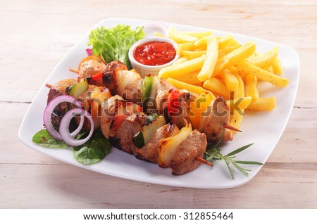 High Angle View of Healthy Kebab Dinner - Skewers of Meat and Vegetables Served with French Fries and Ketchup Dipping Sauce Served on White Plate - stock photo