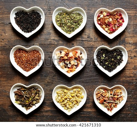 High Angle View of Heart Shaped Dishes Filled with Various Types of Herbal and Black Teas and Arranged on Rustic Wooden Table - stock photo