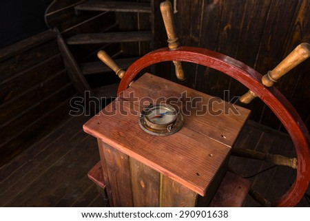 High Angle View of Helm of Antique Wooden Ship with Compass and Steering Wheel on Deck - stock photo