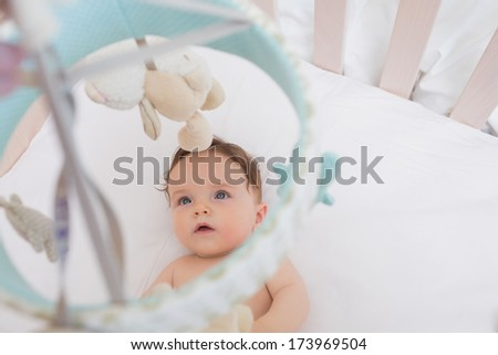 High angle view of innocent baby boy looking at toys hanging in crib - stock photo