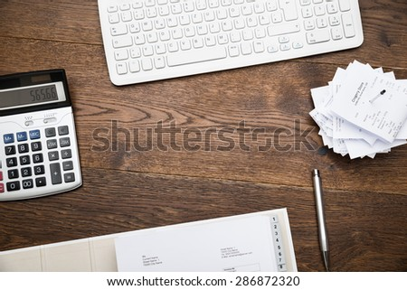 High Angle View Of Keyboard And Calculator With Receipts On Desk - stock photo