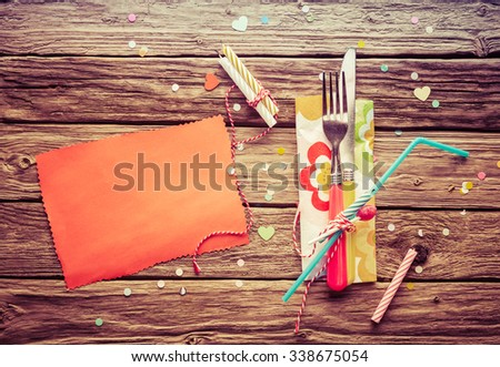 High Angle View of kid or children Birthday Celebration Table Setting - Overview of Knife and Fork Bound by String to Straw and Napkin on Wooden Table with Blank Orange Card  with Candles and Confetti - stock photo