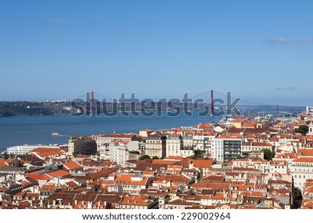 High angle view of Lisbon city with The 25 de Abril Bridge in background against blue sky; Portugal; Europe - stock photo