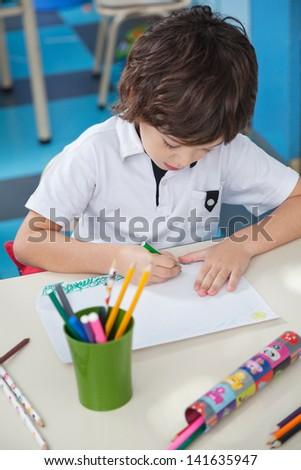 High angle view of little boy drawing at desk in art class