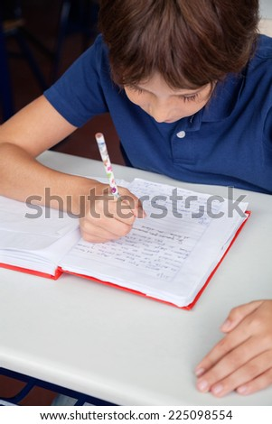 High angle view of little schoolboy reading book at desk in classroom - stock photo